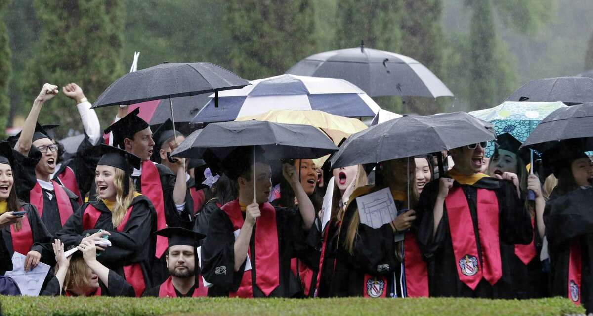 Graduates cheer from under umbrellas during commencement ceremonies on the quad at Rice University Saturday, May. 11, 2019 in Houston, TX.