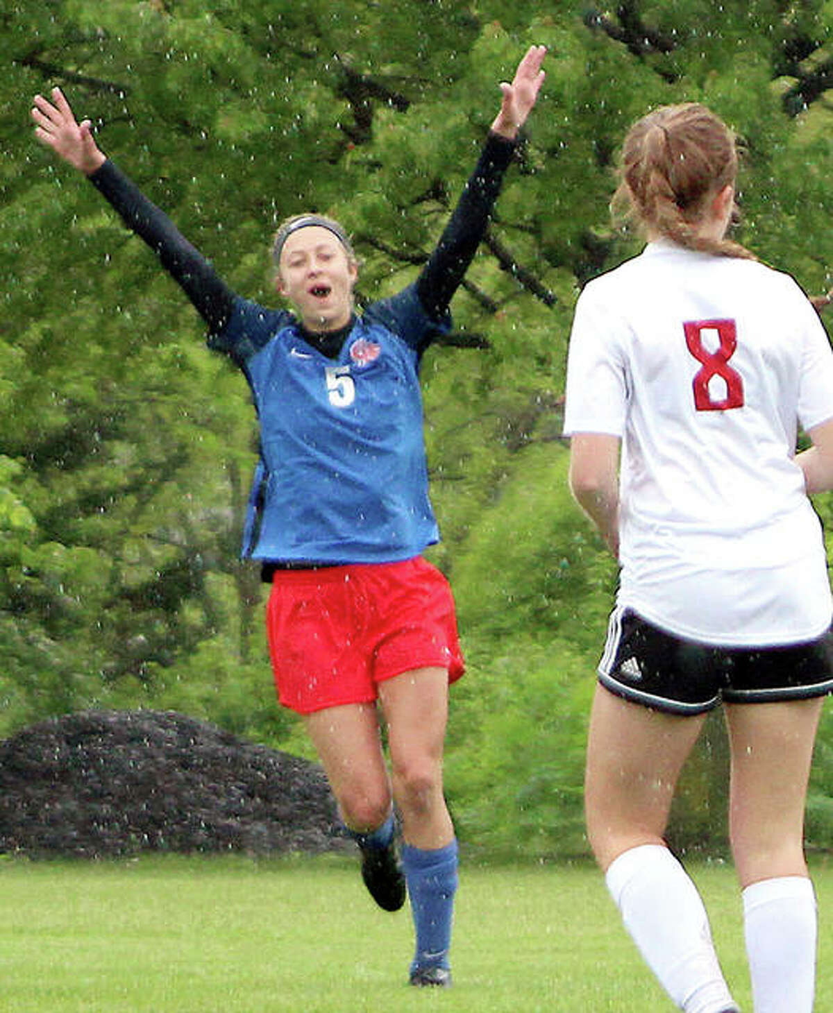 Adriann Welte of Carlinville celebrates after assisting on teammate Lexi West's goal in the second half of Saturday's Carlinville 1A Regional title game at Loveless Park. Also shown is Staunton's Erica Pickerell (8).