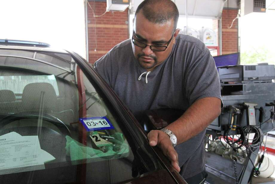 Johnny Pulido, a state vehicle inspector, removes two expired stickers Wednesday, March 2, 2016, in Houston. Texas moved to a single-sticker system for vehicle registrations and inspections a year ago. ( Jon Shapley / Houston Chronicle ) Photo: Jon Shapley, Staff / Houston Chronicle / © 2015  Houston Chronicle