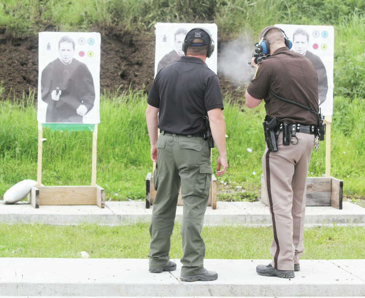 Madison County Sheriff's Deputy Ben Patterson fires an AR-15 at the departments firing range as Range Officer Lt. Roy Pickerill watches. Patterson was qualifying with his duty weapons Thursday, something all the departments officers do twice yearly. The range, located on part of an old Nike Missile base in Marine, is undergoing a number of improvements.