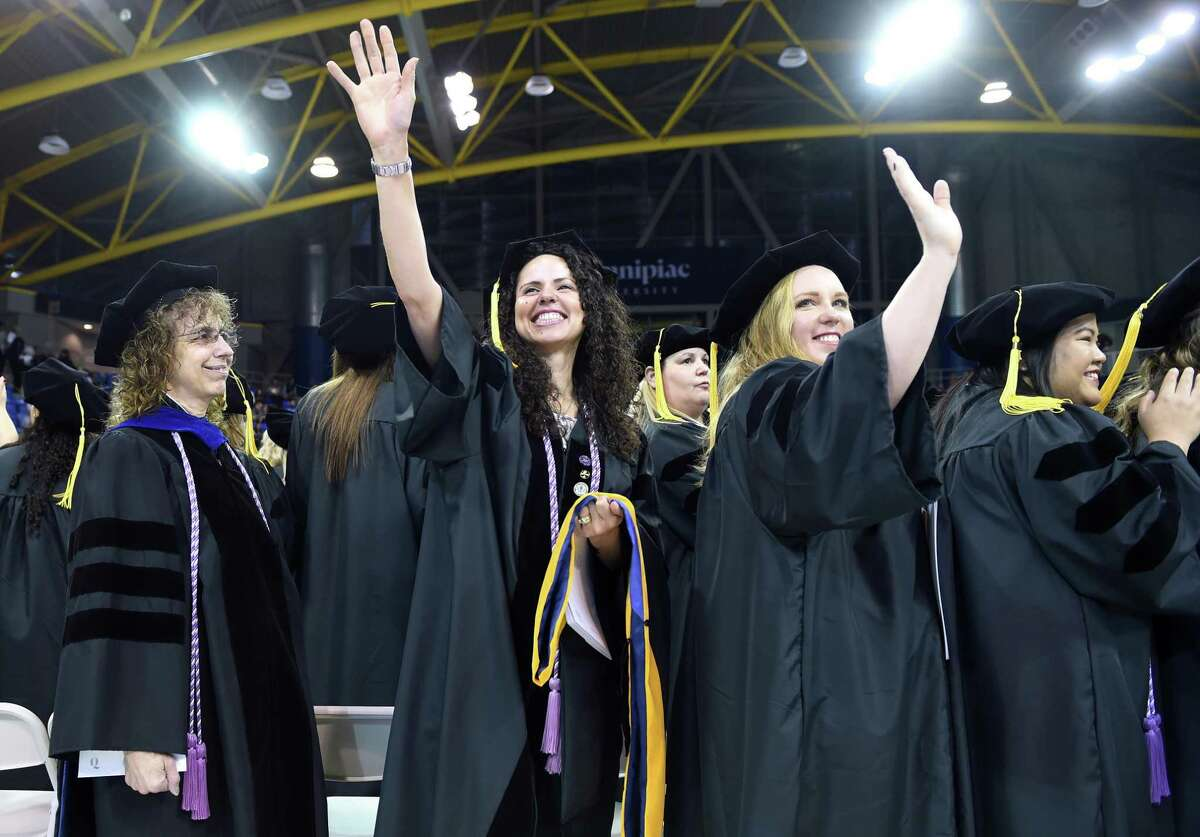 Ines Zemaitis (center left) and Katie Vigil (center right) wave to family at the Quinnipiac University Graduate Commencement Exercises for the College of Arts and Sciences, School of Health Sciences and School of Nursing at the People's United Center in Hamden on May 11, 2019. Zemaitis and Vigil received Doctor of Nursing Practice degrees.