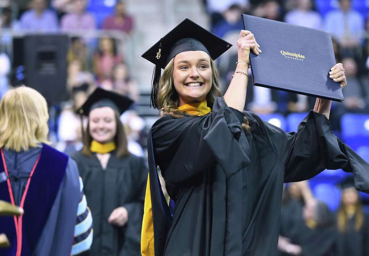 Laura Van Horn holds up her Master of Occupational Therapy degree at the Quinnipiac University Graduate Commencement Exercises for the College of Arts and Sciences, School of Health Sciences and School of Nursing at the People's United Center in Hamden on May 11, 2019.
