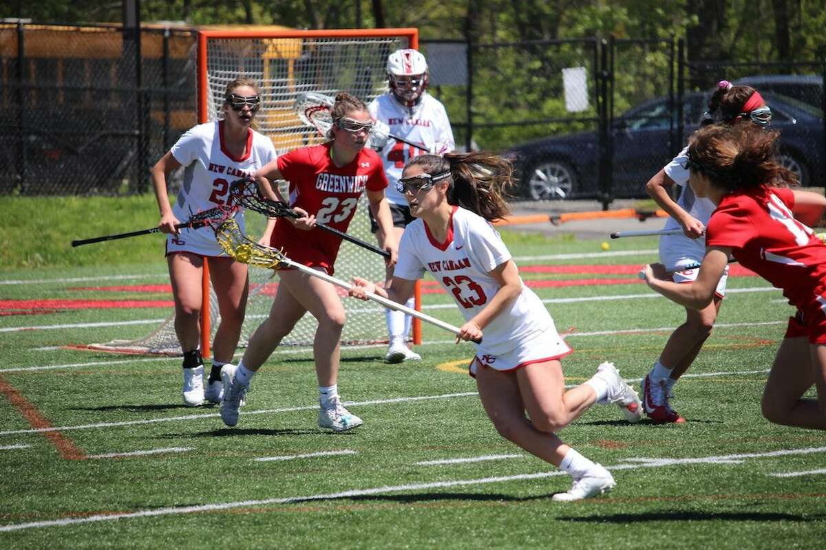 New Canaan's Natalie Lopez (23) scoops up a ground ball on Saturday against visiting Greenwich.