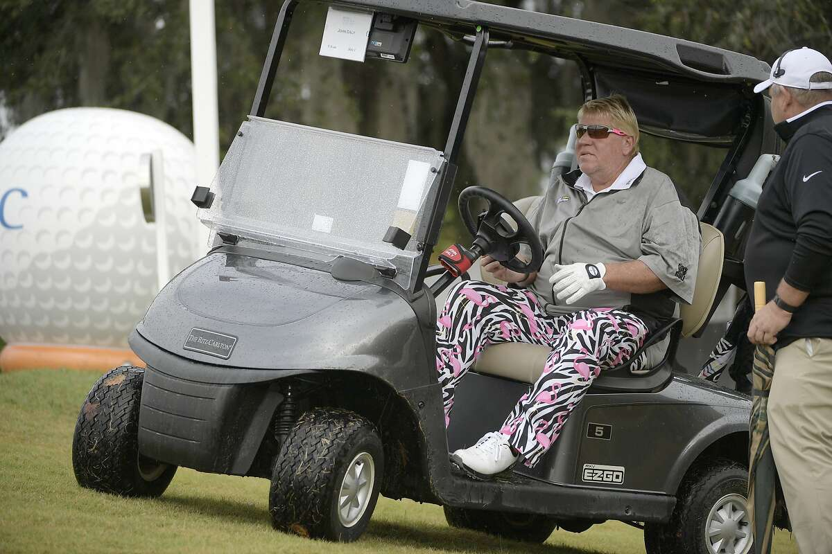 FILE - In this Dec. 15, 2018, file photo, John Daly drives in his cart after hitting a tee shot on 10th hole during the first round of the Father Son Challenge golf tournament in Orlando, Fla. The PGA Championship is allowing Daly to use a cart next week at Bethpage Black. It will be the first time since Casey Martin in the U.S. Open in 2012 that a player is allowed to ride a cart during a major. (AP Photo/Phelan M. Ebenhack, File)