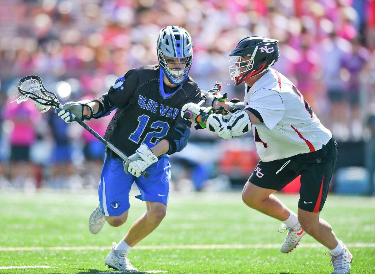 Darien's Tommy Hellman moves upfield against New Canaan's Christian Sweeney during game at Duning Field on May 11 in New Canaan.