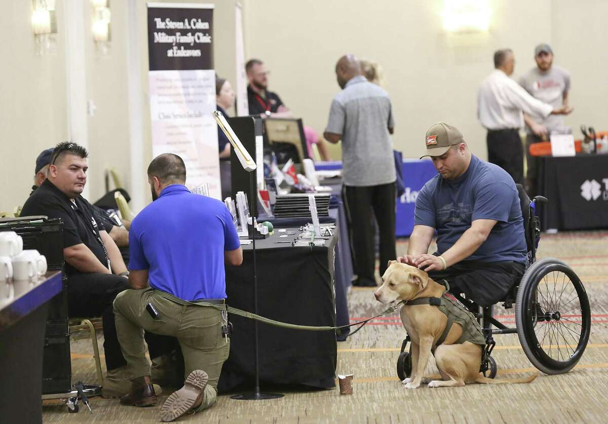 Sgt. Shane Parsons pets service dog Daffodil at the Resiliency Resource Fair at the Houston Marriott on May 11, 2019 in Houston, TX.