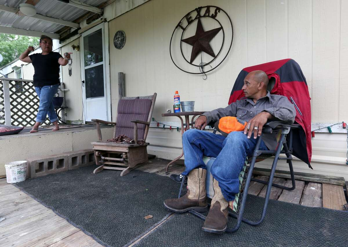 Veronica, left, and Edward Williams talk Tuesday, May 7, 2019 on their front porch in Gillett in Karnes County about seeing the recent multi-agency raid across the street from their home that busted a cockfighting ring.