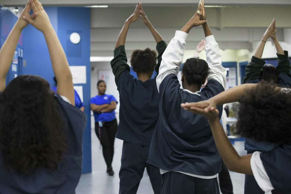 Harris County Juvenile Detention Center girls stretch with Houston Ballet instructors at the beginning of a dance class on Friday, April 5, 2019, in Houston. The center has been increasing art and culture programs for the teenagers.