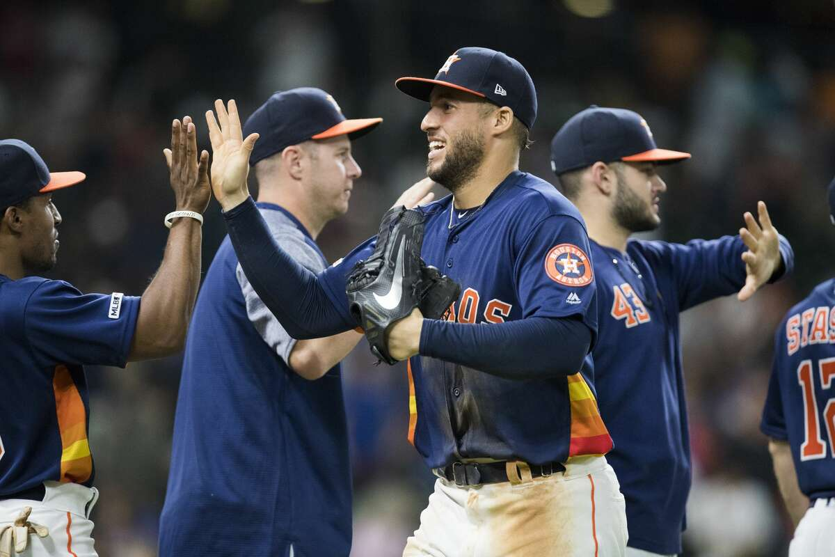 Houston Astros center fielder George Springer (4) high fives his teammates after winning the game 11-4 against the Texas Rangers at Minute Maid on Saturday, May 11, 2019, in Houston.