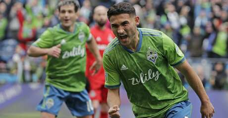 Seattle Sounders midfielder Cristian Roldan, right, and Nicolas Lodeiro, left, react after Roldan scored a goal against Toronto FC during the second half of an MLS soccer match, Saturday, April 13, 2019, in Seattle. The Sounders won 3-2. (AP Photo/Ted S. Warren)