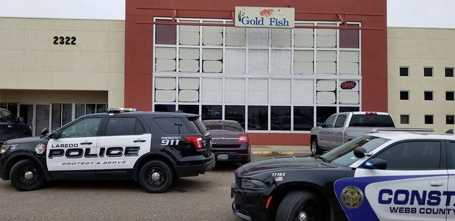 Law enforcement could be seen outside the Gold Fish on Jacaman Road. The Gold Fish is one of five locations raided on Friday afternoon as part of Operation One-Armed Bandit. Photo: Courtesy