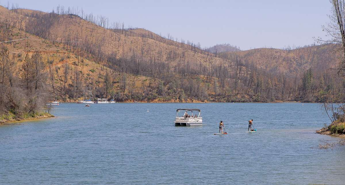 A patio boat, a couple on Stand Up Paddleboards and kayakers venture out at Oak Bottom Marina, with the lake full and signs of last year's Carr Fire in the background