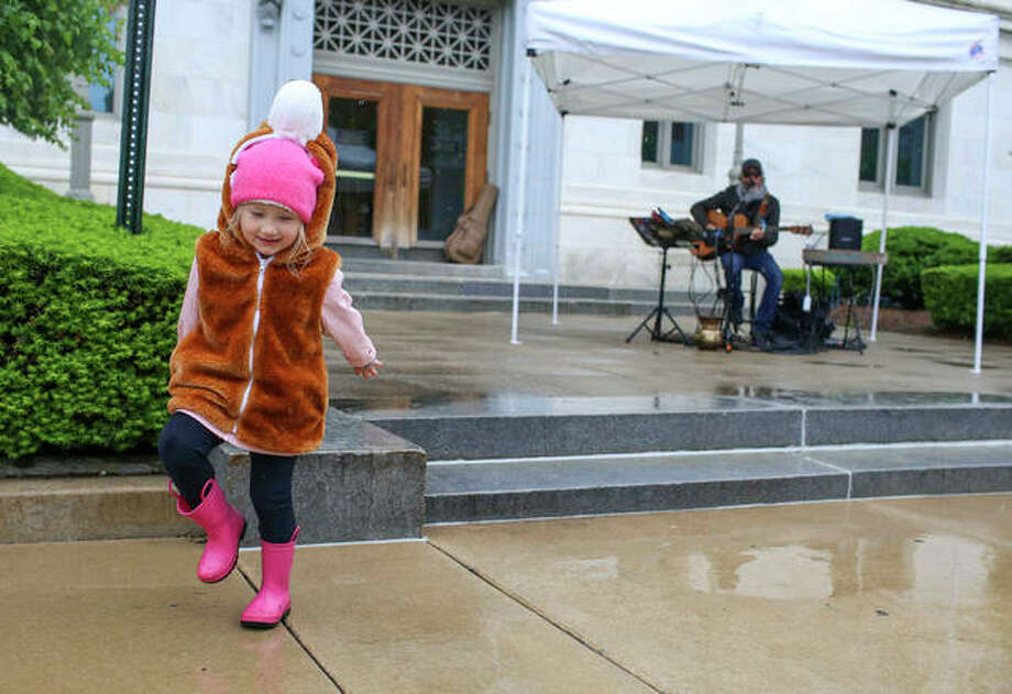 Valerie Van Daley, age 4, dances and splashes in puddles while listening to local musician Butch Moore play some tunes at the Goshen Market on Saturday morning. Photo: Marci Winters-McLaughlin | For The Intelligencer