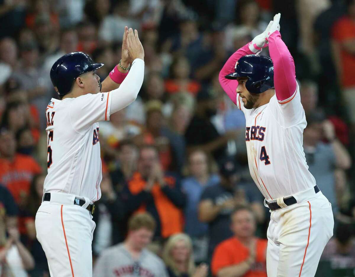 Houston Astros center fielder George Springer (4) celebrates his two-run home run with Houston Aledmys Diaz (16) during the bottom sixth inning against the Texas Rangers at Minute Maid Park on Sunday, May 12, 2019, in Houston.