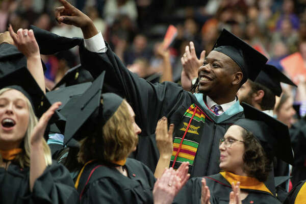Students rise to thank their parents and family at the evening Graduate commencement Friday at SIUE.