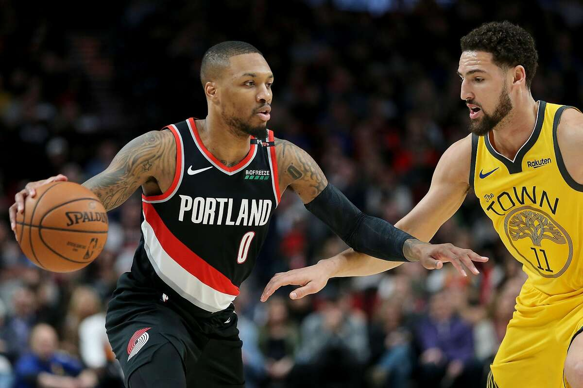 PORTLAND, OR - FEBRUARY 13: Damian Lillard #0 of the Portland Trail Blazers dribbles against Klay Thompson #11 of the Golden State Warriors in the first half during their game at Moda Center on February 13, 2019 in Portland, Oregon. NOTE TO USER: User exp