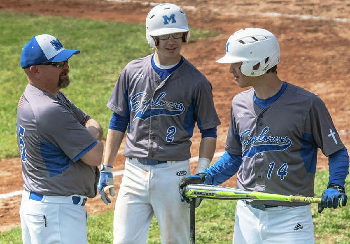 Marquette Catholic coach Tim Fahnestock chats with Braden Coles (2) and Kollin Morrissey (14) during a game earlier this season at Hopkins Field in Alton. The 21-9 Explorers open Class 2A postseason play this week at the Staunton Regional.