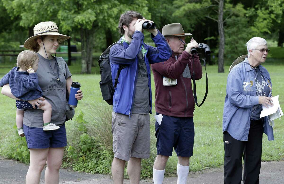 (From left) Isaac Touzel, age 11 mos., held by his mother Marla Touzel, Joseph Touzel, Tim Touzel and Marion Touzel spot and identify birds as they compete in The Great Texas Birding Classic at Sheldon Lake State Park Sunday, May. 12, 2019 in northeast Houston, TX.