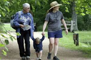 Grandmother Marion Touzel and mother Marla Touzel hold hands with 11 month old Isaac Touzel as they walk trails while competing in The Great Texas Birding Classic at Sheldon Lake State Park Sunday, May. 12, 2019 in northeast Houston, TX.