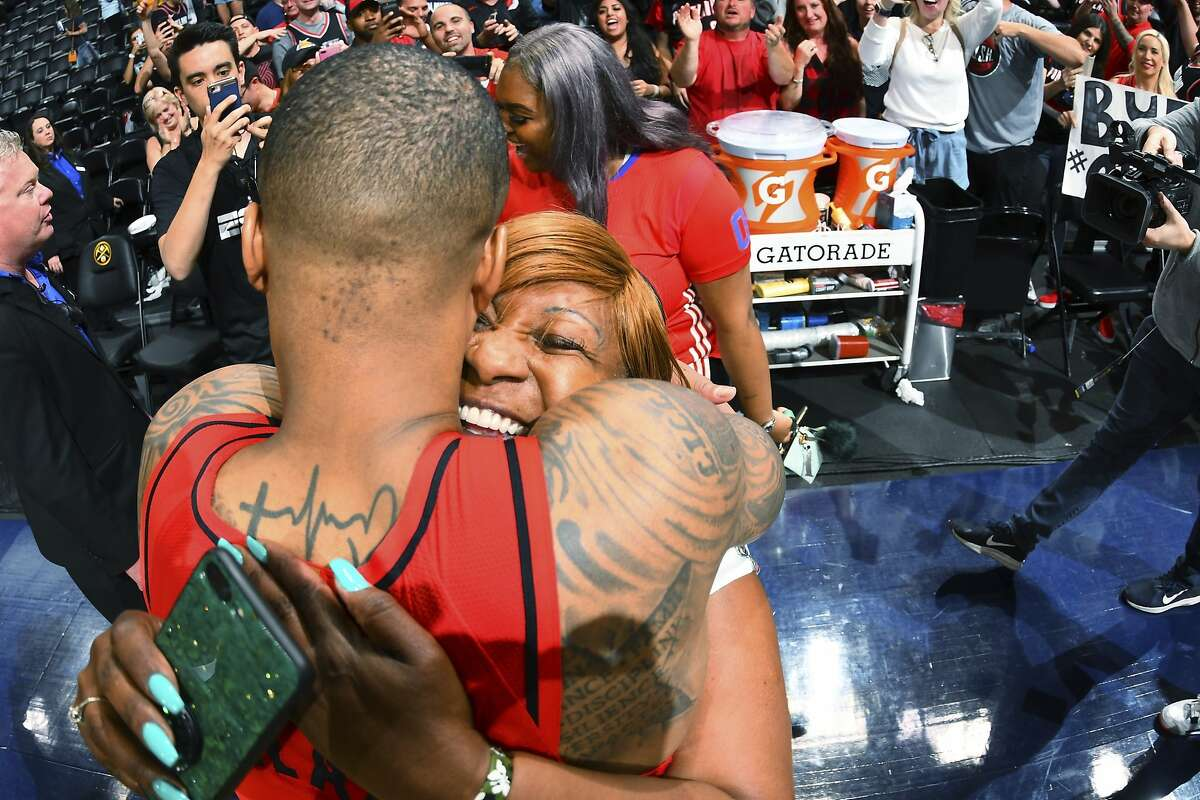 Portland Trail Blazers guard Damian Lillard is hugged by his mother, Gina Johnson, after the second half of Game 7 of an NBA basketball second-round playoff series Sunday, May 12, 2019, in Denver. The Trail Blazers won 100-96. (AP Photo/David Zalubowski)