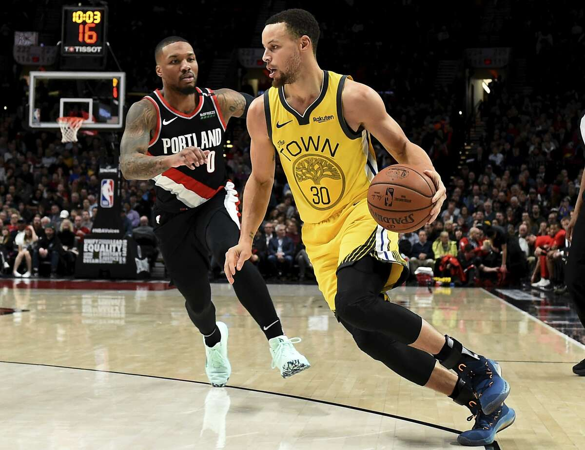 Golden State Warriors guard Stephen Curry, right, drives to the basket past Portland Trail Blazers guard Damian Lillard during the first half of an NBA basketball game in Portland, Ore., Wednesday, Feb. 13, 2019. (AP Photo/Steve Dykes)