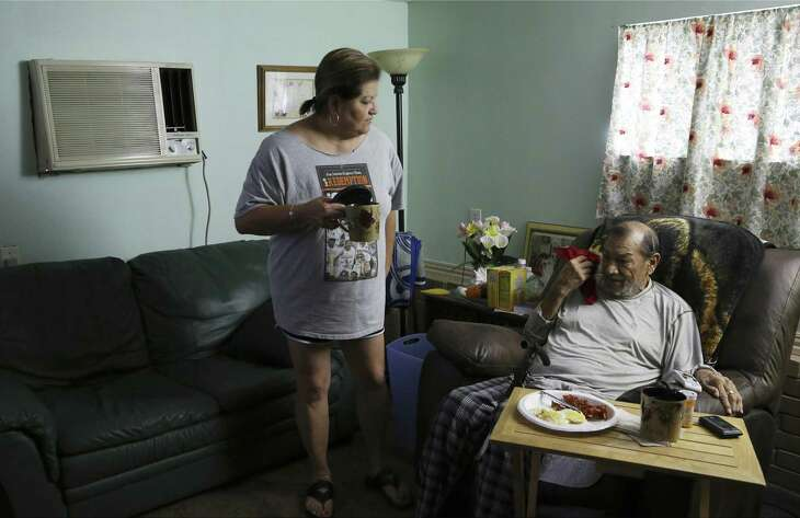 Susan Martinez serves breakfast to her husband, Alex Silva. Martinez does not have health insurance, and Silva is on hospice care. She faces a $7,406 hospital bill for a trip to the ER for walking pneumonia, but she's not sure how she'll pay.