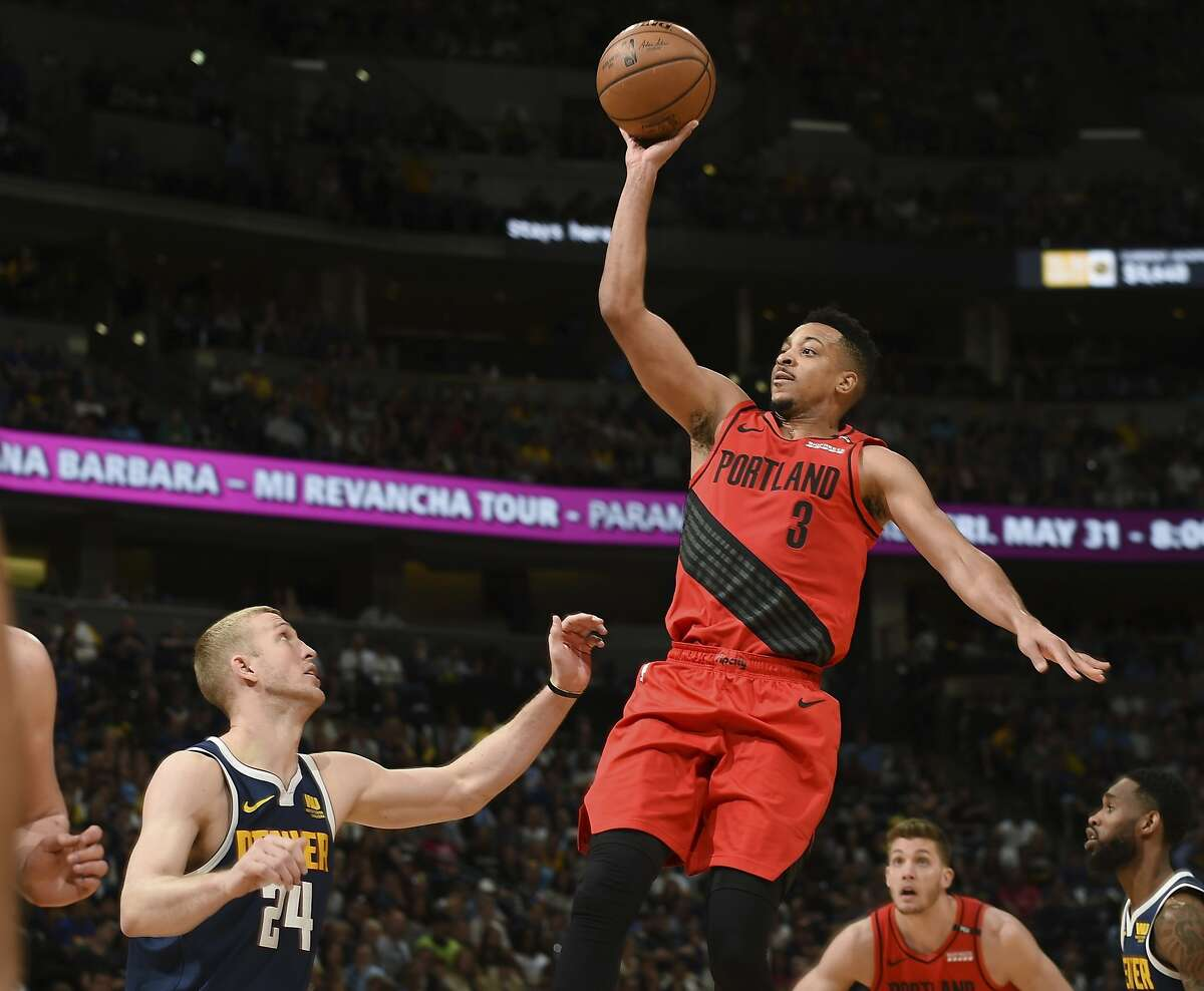 Portland Trail Blazers guard CJ McCollum, right, flies over Denver Nuggets forward Mason Plumlee for a basket in the second half of Game 7 of an NBA basketball second-round playoff series Sunday, May 12, 2019, in Denver. The Trail Blazers won 100-96. (AP Photo/John Leyba)
