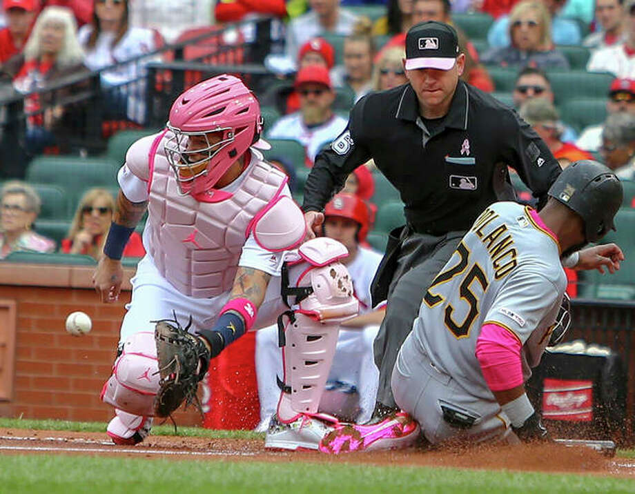 Cardinals catcher Yadier Molina (left) waits for the ball as the Pirates' Gregory Polanco (25) slides home with a run during the first inning Sunday at Busch Stadium. Photo: Scott Kane / Associated Press