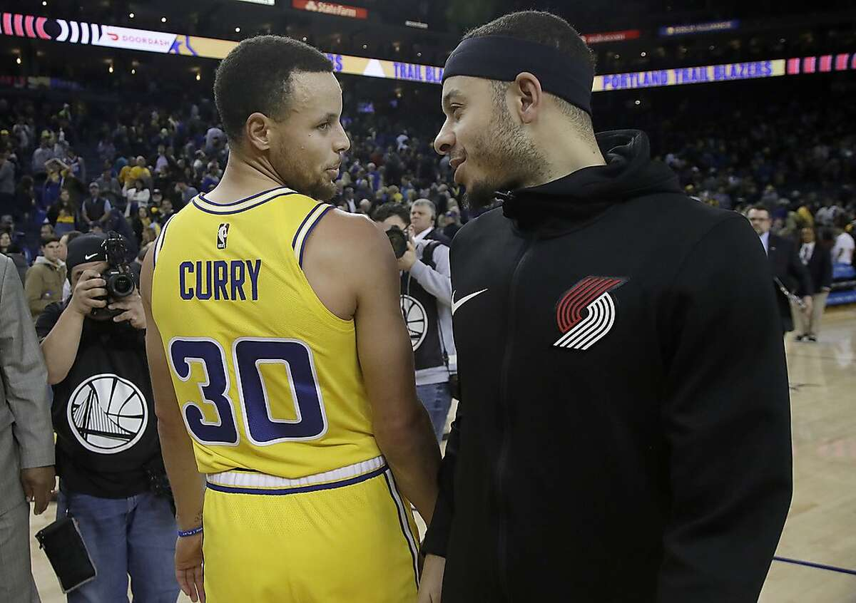 FILE - In this Dec. 27, 2018, file photo, Golden State Warriors guard Stephen Curry (30) talks with his brother Portland Trail Blazers guard Seth Curry after an NBA basketball game in Oakland, Calif. The Curry brothers will take part in the 3-point contest during All-Star weekend. (AP Photo/Jeff Chiu, File)