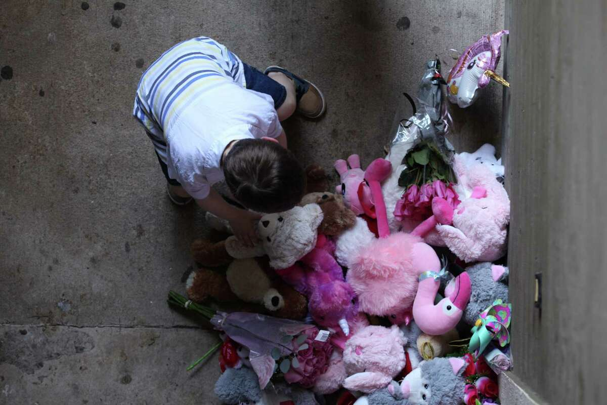 Lyrik Shane, 5, places a teddy bear at a tribute to Maleah Davis at her family's door step in the 9800 block of Kingwood Drive on May 12, 2019.