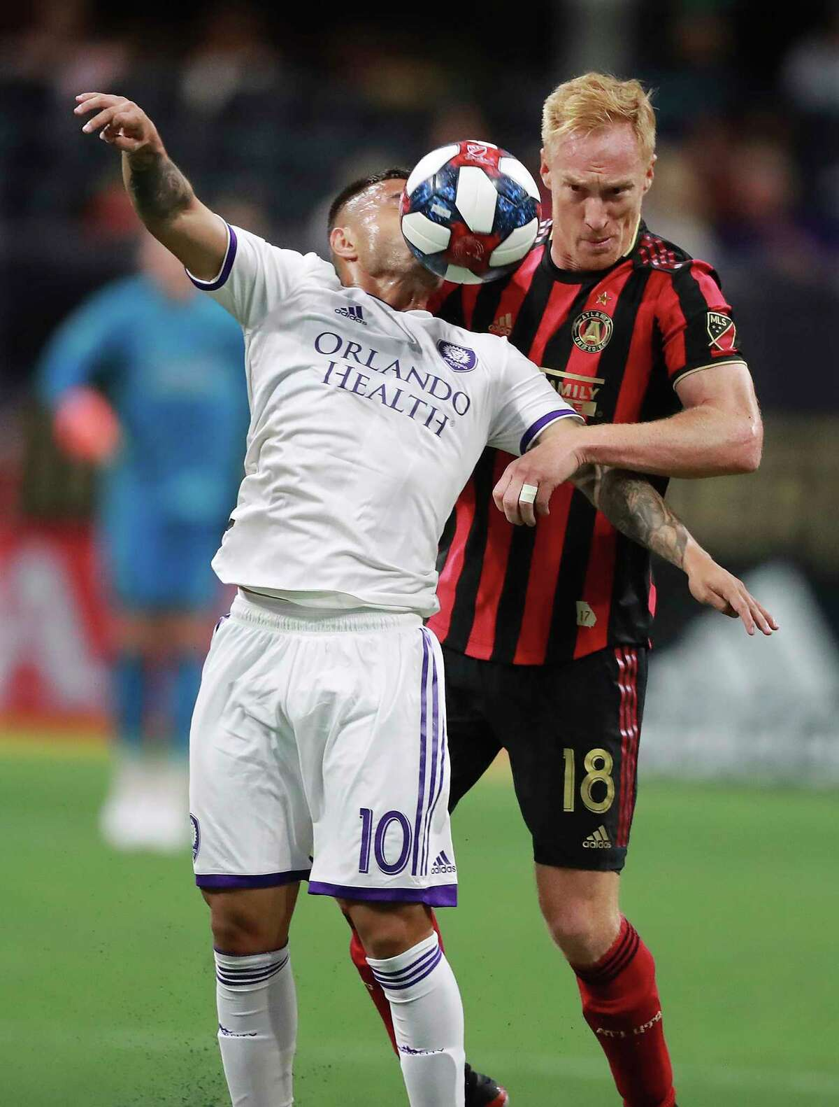 Atlanta United midfielder Jeff Larentowicz, who made his 400th MLS game played, battles Orlando City midfielder Josue Colman for the ball during the second half in a MLS soccer match on Sunday, May 12, 2019, in Atlanta. Atlanta United won the game 1-0. (Curtis Compton/Atlanta Journal-Constitution via AP)