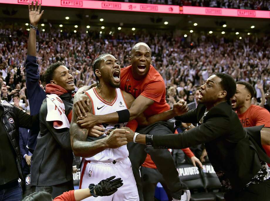 Kawhi Leonard, second from left, celebrates after his basket gave the Raptors a win over the 76ers in Game 7 of an Eastern Conference semifinals series. Toronto will face Milwaukee in the East finals. Photo: Frank Gunn / Associated Press