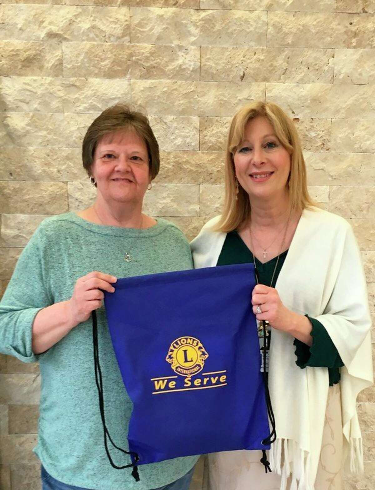 Carlene Skorczewski, manager of MidMichigan Health Foundation, accepts Lions Club hospital bags for children from Shiela Ferrel. (Photo provided)