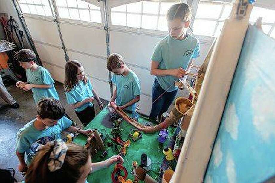 Members of the Homeschool STEAM Alliance, Jillian Barlow (clockwise from bottom), Sam Boesch, Miles Remenji, Cadence Fricke, Sam Earales and Olivia Remenji, help set up their invention in Champaign for the first time since competing in the national 2019 Rube Goldberg Machine Contest. Photo: Stephen Haas | News-Gazette (AP)