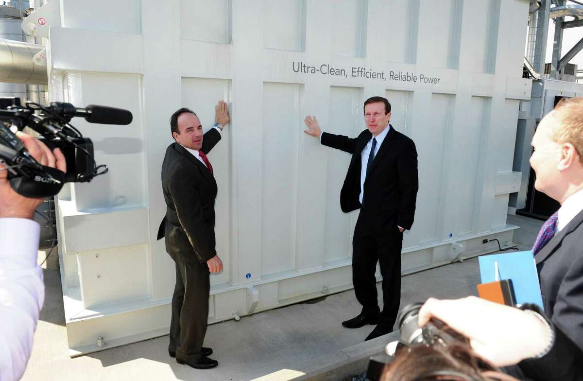Bridgeport Mayor Joe Ganim, left, and US Senator Chris Murphy lean against Dominion's 14.9 Megawatt FuelCell during an Eco-Technology Park Tour in Bridgeport, Conn., on Wednesday Mar. 23, 2016. The tour, offered by the Bridgeport Regional Business Council, took city officials, developers and local business people on a bus tour to several actual site producing green energy as well as some proposed future sites.