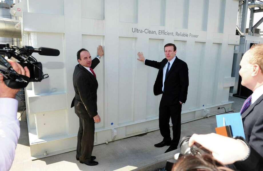 Bridgeport Mayor Joe Ganim, left, and US Senator Chris Murphy lean against Dominion's 14.9 Megawatt FuelCell during an Eco-Technology Park Tour in Bridgeport, Conn., on Wednesday Mar. 23, 2016. The tour, offered by the Bridgeport Regional Business Council, took city officials, developers and local business people on a bus tour to several actual site producing green energy as well as some proposed future sites. Photo: Christian Abraham / Hearst Connecticut Media / Connecticut Post
