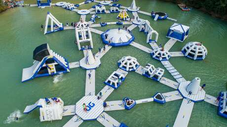 """Dubbed the the """"largest inflatable obstacle course in Texas,"""" the park's """"Wild Isle"""" ride challenges participants to master 54 inflatable obstacleson top of a spring-fed lake."""