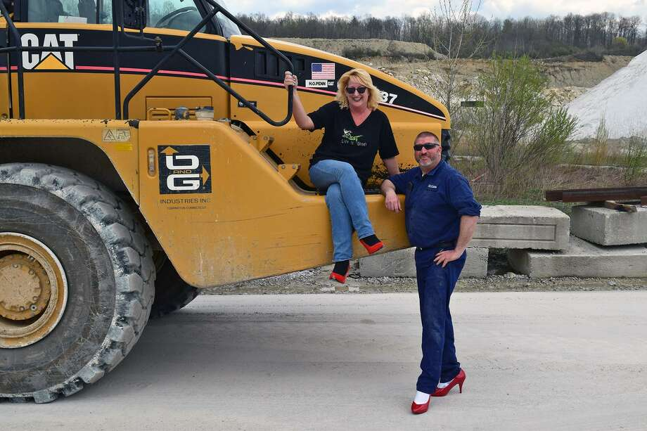 Haul Truck Operator Kim Paolino and Quarry Supervisor Dave Guerrera of O& Industries pose in red high heels at the company's New Milford Quarry to promote the 2018 Susan B. Anthony Project's Walk a Mile In Her Shoes event, held to raise funds and awareness to stop rape, sexual assault and gender violence. This year's event will be held May 19, 2019 in Litchfield. Photo: Contributed Photo /