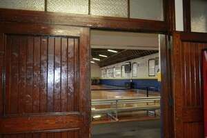 The modern basketball court seen through the original, thick hardwood doors of the Torrington Armory.