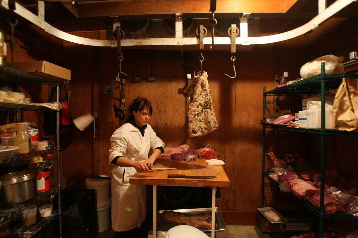 MEATPACKER_0124_LKM.jpg Tia Harrison cleans out the freezer at Avedano's Holly Park Market in Bernal Heights. Harrison runs the meat market with two other women. (Laura Morton/Special to the Chronicle)