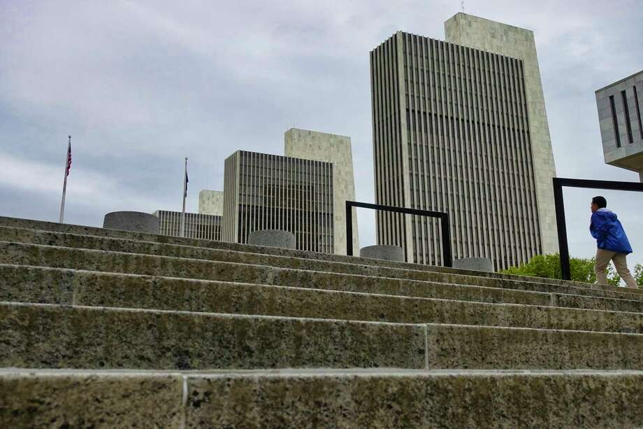 If you take a walk Wednesday morning, you might see the sun. In this photograph, a man makes his way up the stairs that lead to the Empire State Plaza on Monday.   (Paul Buckowski/Times Union) Photo: Paul Buckowski, Albany Times Union / (Paul Buckowski/Times Union)