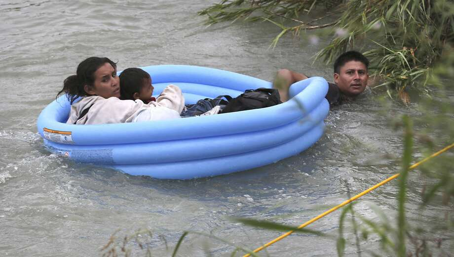 One of the Honduran fathers, pulls his wife and two children, ages 2 and 4, to safety on the U.S. side in Eagle Pass. Photo: Bob Owen
