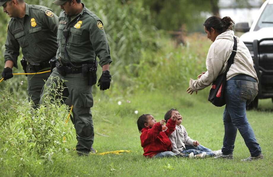 Once safely on shore, the mother tries to comfort her terrified children. The group assembled on the grass, right by an Eagle Pass golf course. Migrants are crossing the swollen Rio Grande in this Border Patrol district every day, resulting in more than 300 rescues. Photo: Bob Owen