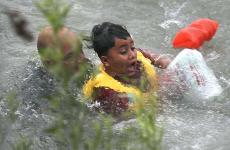 (4.) Border Patrol Agent in Charge Bryan Kemmett, left, passes the boy to another agent on land after rescuing him. A total of nine people were helped out of the river.