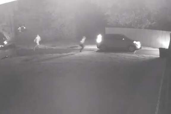 The two masked men can be seen on video running up to the parked car and yanking open the passenger and driver side doors before demanding cash and cell phones.