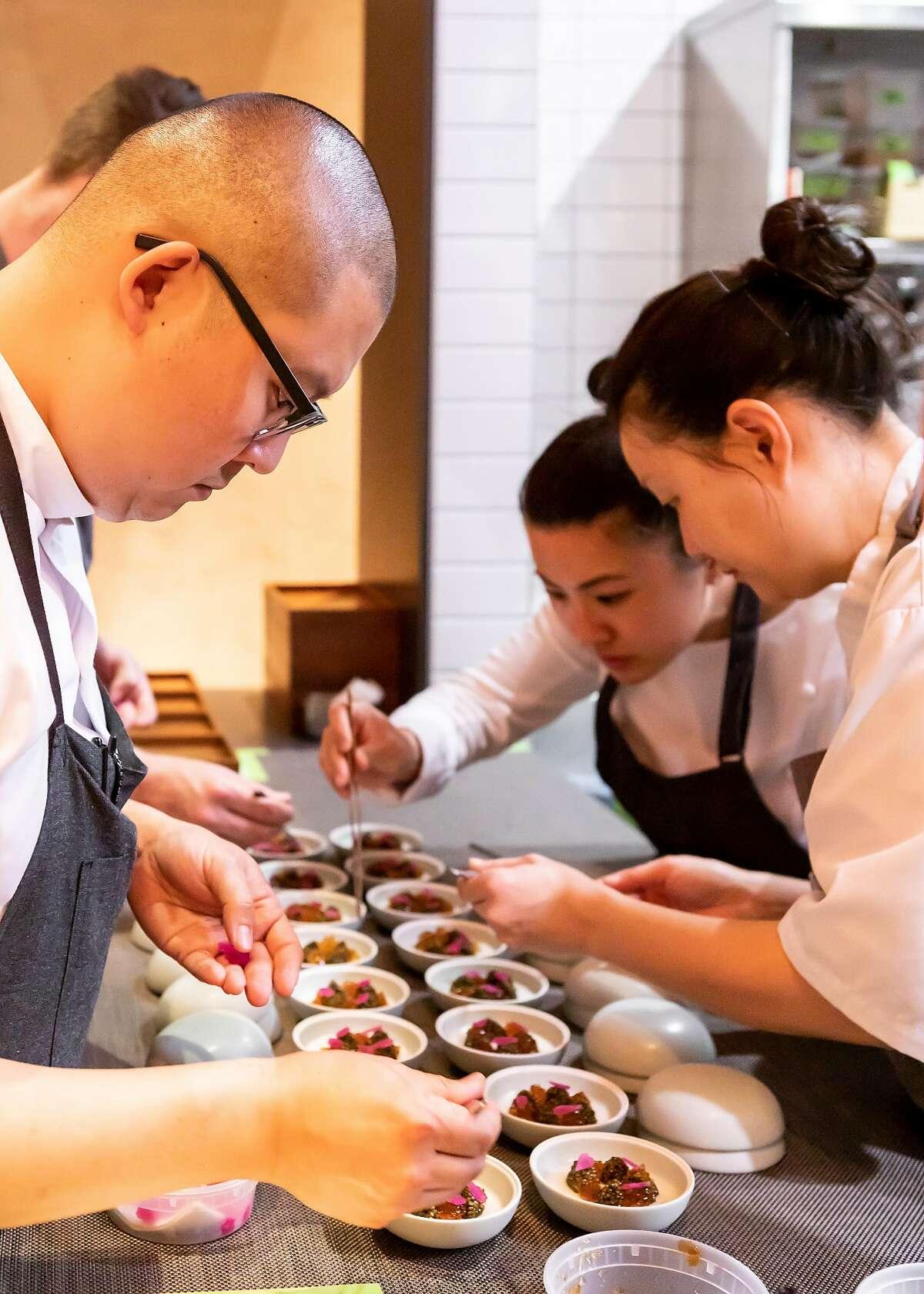 Chefs prepare courses at Maum in Palo Alto, Calif. on Friday, April 26, 2019.