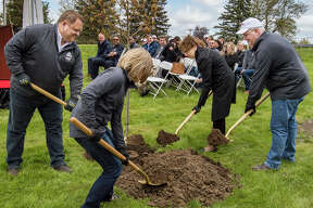 "DuPont Global Business President and leader of ""DuPont North"" Tim Lacey, left, Midland Mayor Maureen Donker, center right, and DuPont CEO-elect Marc Doyle, right,  plant a red maple sapling during a symbolic ceremony commemorating DuPont's presence in Michigan on Monday near US-10 and North Jefferson Avenue in Midland. (Ashley Schafer/ashley.schafer@hearstnp.com)"