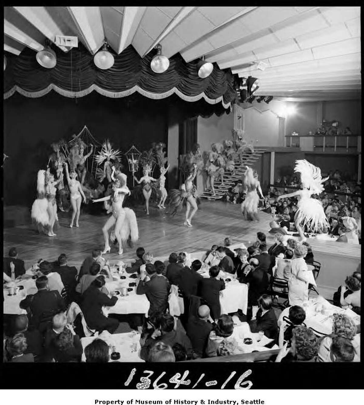 """""""A Night in Paradise"""" was a Las Vegas-style burlesque show performed in Gracie Hansen's Paradise International Theater on Show Street, the adult entertainment area of the 1962 Seattle World's Fair. The plush 700-seat theater offered four shows a night, described as """"extravagant production numbers featuring the world's most beautiful girls, interspersed with internationally renowned specialty performers."""" In this photograph, dancers in flashy costumes perform on stage while the audience, seated at tables, looks on."""