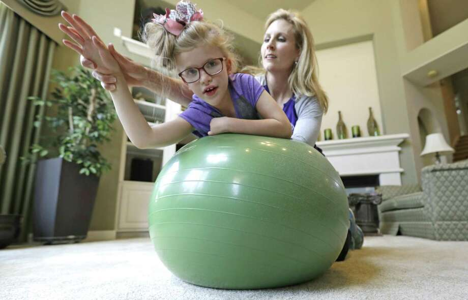 Stacey English, right, works on balance and core strength with her 7-year-old daughter, Addison, in Houston on Friday, June 23, 2017. Texas children with special needs like Addison have lost critical services since the state implemented $350 million in Medicaid cuts to speech, occupational, and physical therapy in December. (AP Photo/David J. Phillip) Photo: David J. Phillip, STF / AP / Internal