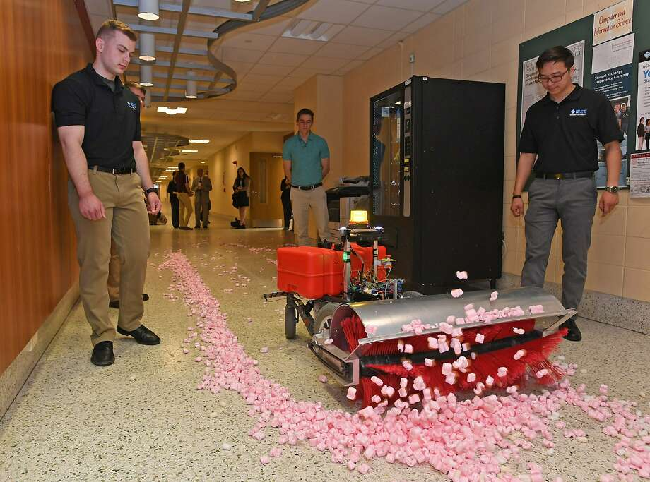 From left: Niklas Bitters, 22; Mitch Wesley, 22; and Tenger Batjargal, 23, watch as an autonomous snow-removal robot moves along a hallway at the Zurn Science Center at Gannon University in Erie, Pa., on May 10, 2019. The Gannon engineering students were part of a team that built the robot during the 2018-19 school year as their senior project, which they presented to faculty on May 10, 2019. The robot is programmed with a route and then sensors keep it on that route. The team says this machine has 16 miles of battery life and can sweep up to four inches of snow. (Christopher Millette/Erie Times-News via AP) Photo: Christopher Millette, Associated Press